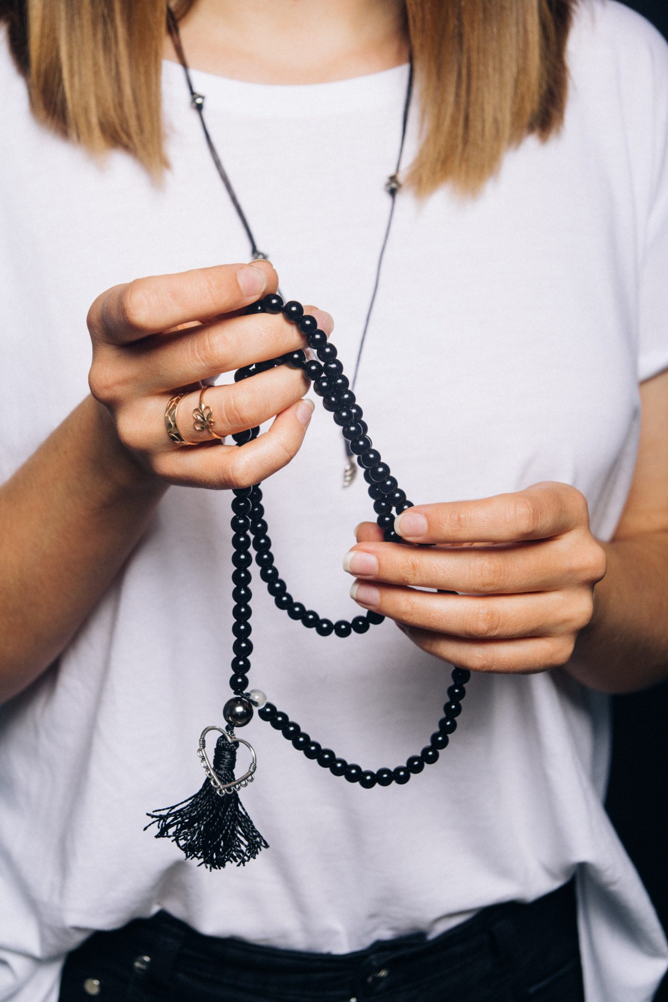 Black beads bracelet in girl hand. Can be used as fashion accessories, also as praying beads, for counting prayers or practicing mindfulness meditation. Some believe black stone has protection power