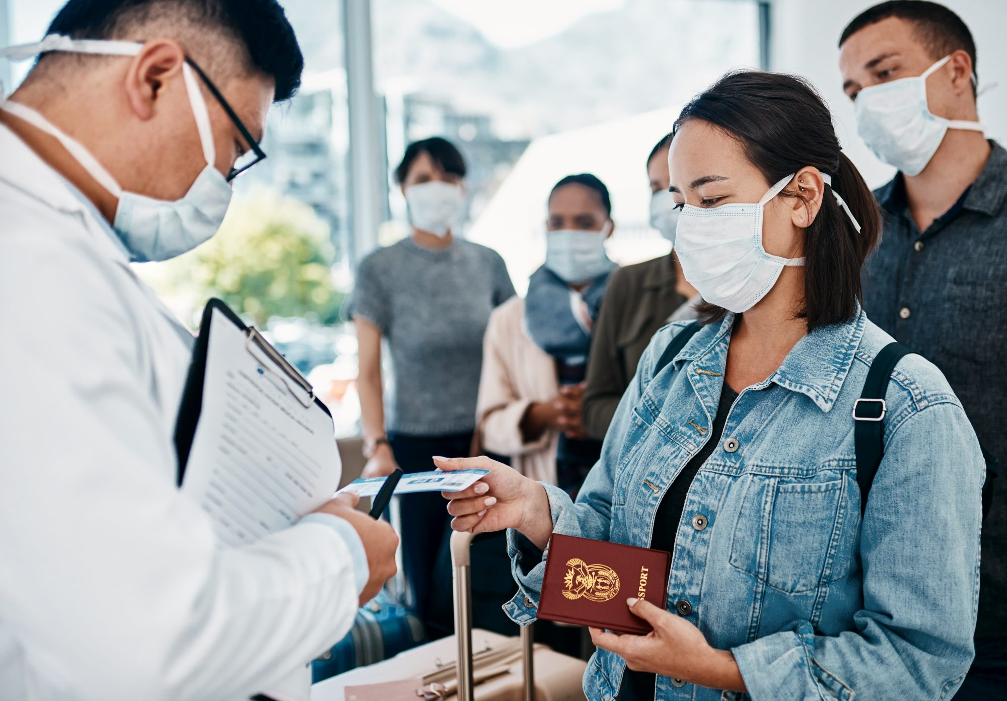 Shot of a woman wearing a mask and giving her passport to a doctor in an airport