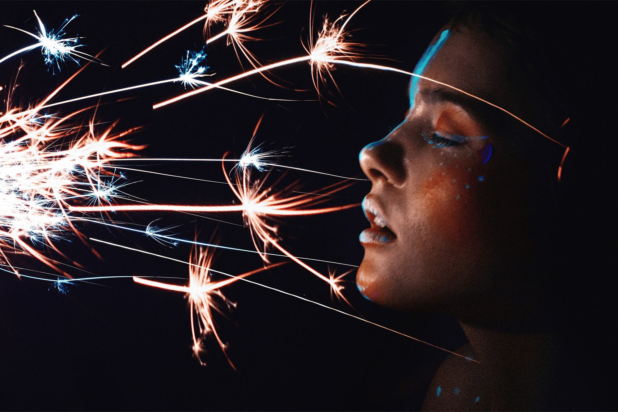 Beautiful woman with uv make-up and sparkler