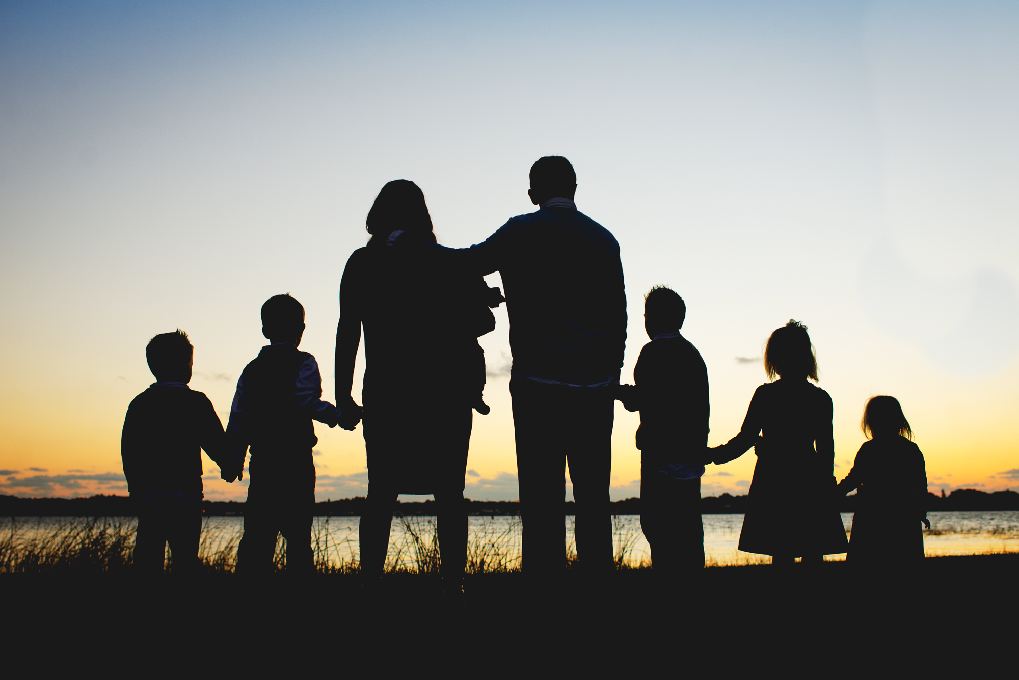Mom of 8 Dies of COVID , Family with six kids look at setting sun on a lake in Florida