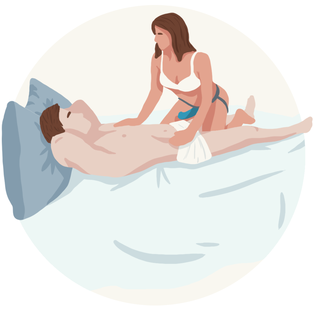 Woman wearing strap-on in bed above man
