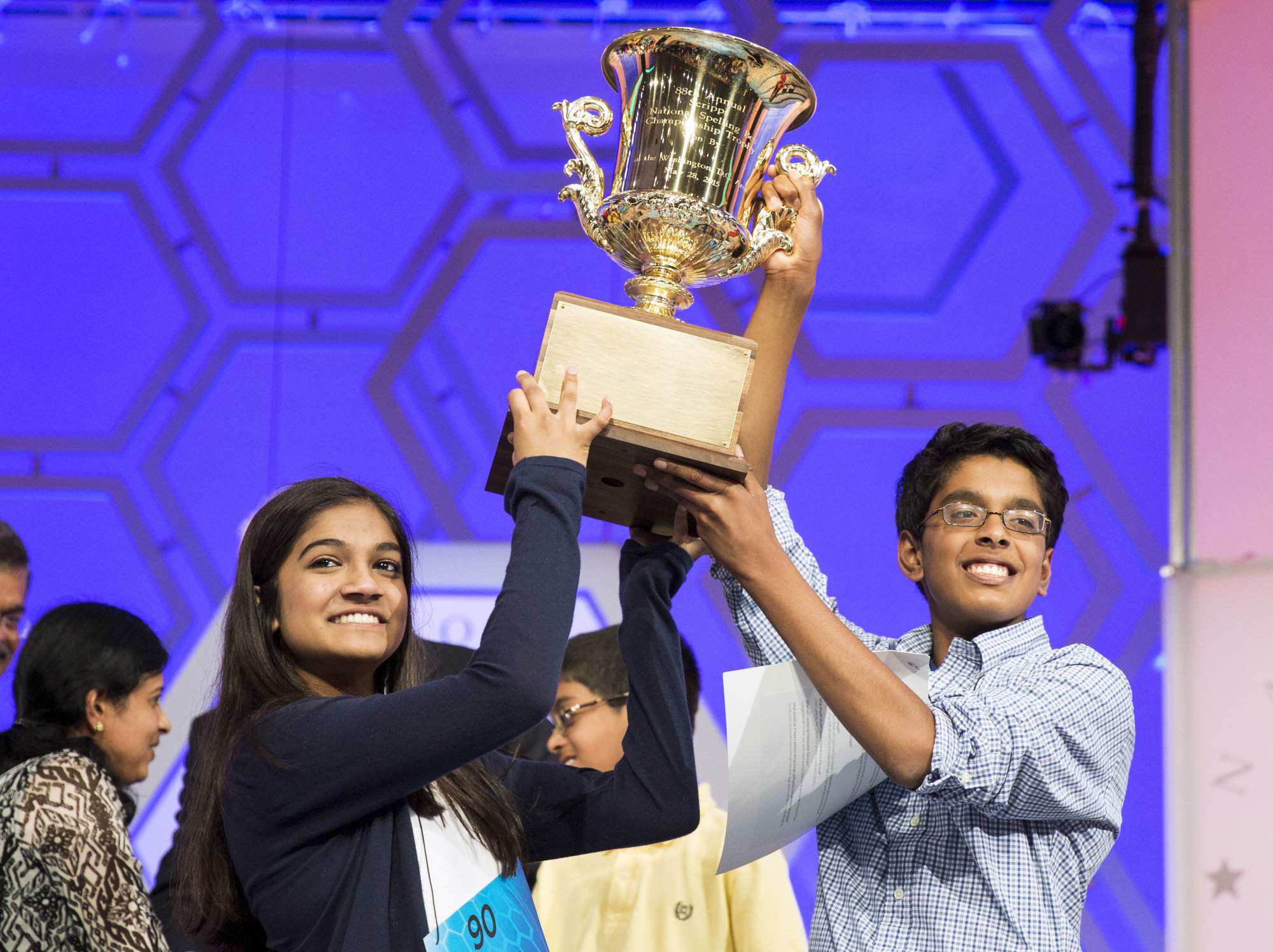 Vanya Shivashankar of Olathe, Kansas, and Gokul Venkatachalam, St. Louis Missouri lift the trophy after becoming co-champions after the final round of the 88th annual Scripps National Spelling Bee