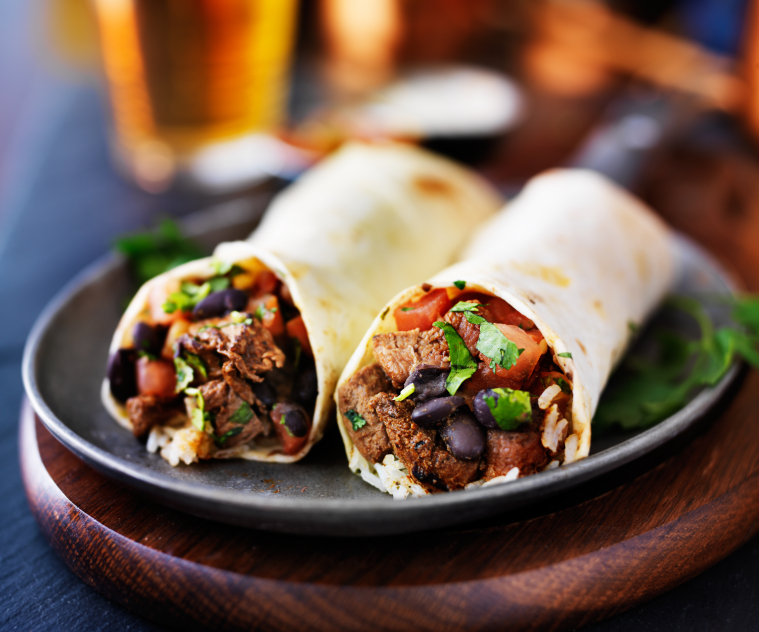mexican beef burritos with beer in background