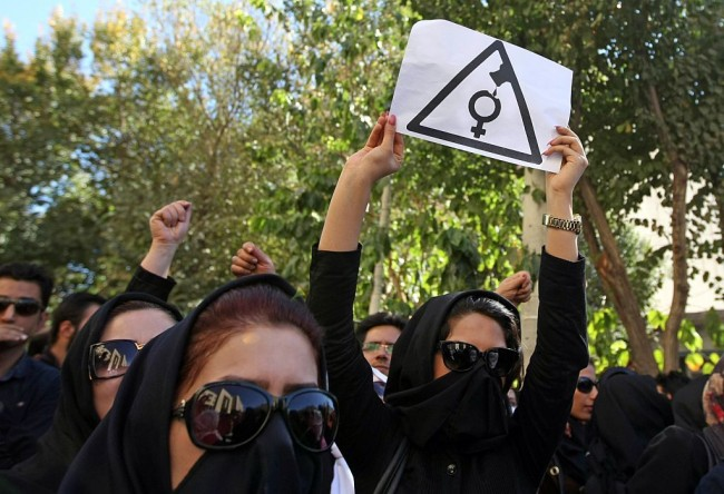 Iranian women, hiding their faces not to be identified, shout slogans during a protest in front of the judiciary building on October 22, 2014 in Isfahan, 450 kilometres south of Tehran, in solidarity with women injured in a series of acid attacks. Around 1,000 people took part in the protest calling for better security with banners and placards demanding action after four women have been maimed by assailants on motorcycles who threw acid on them. The acid attacks have prompted speculation on social networks that the victims were targeted because they were