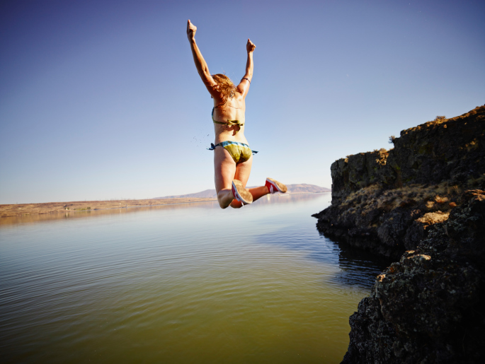 Young woman jumping off edge of cliff into river with arms overhead