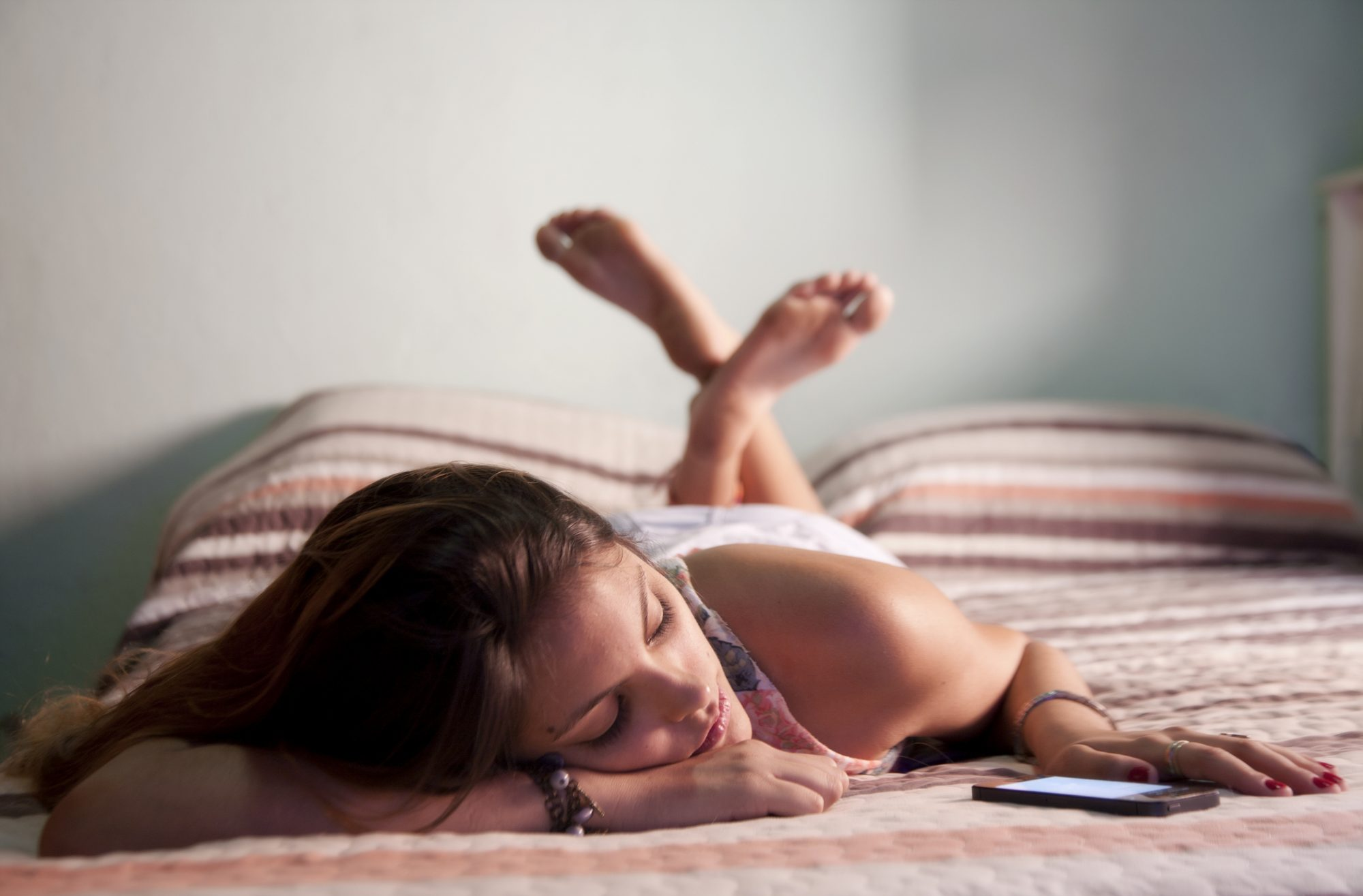 Girl laying on bed looking at her mobile phone