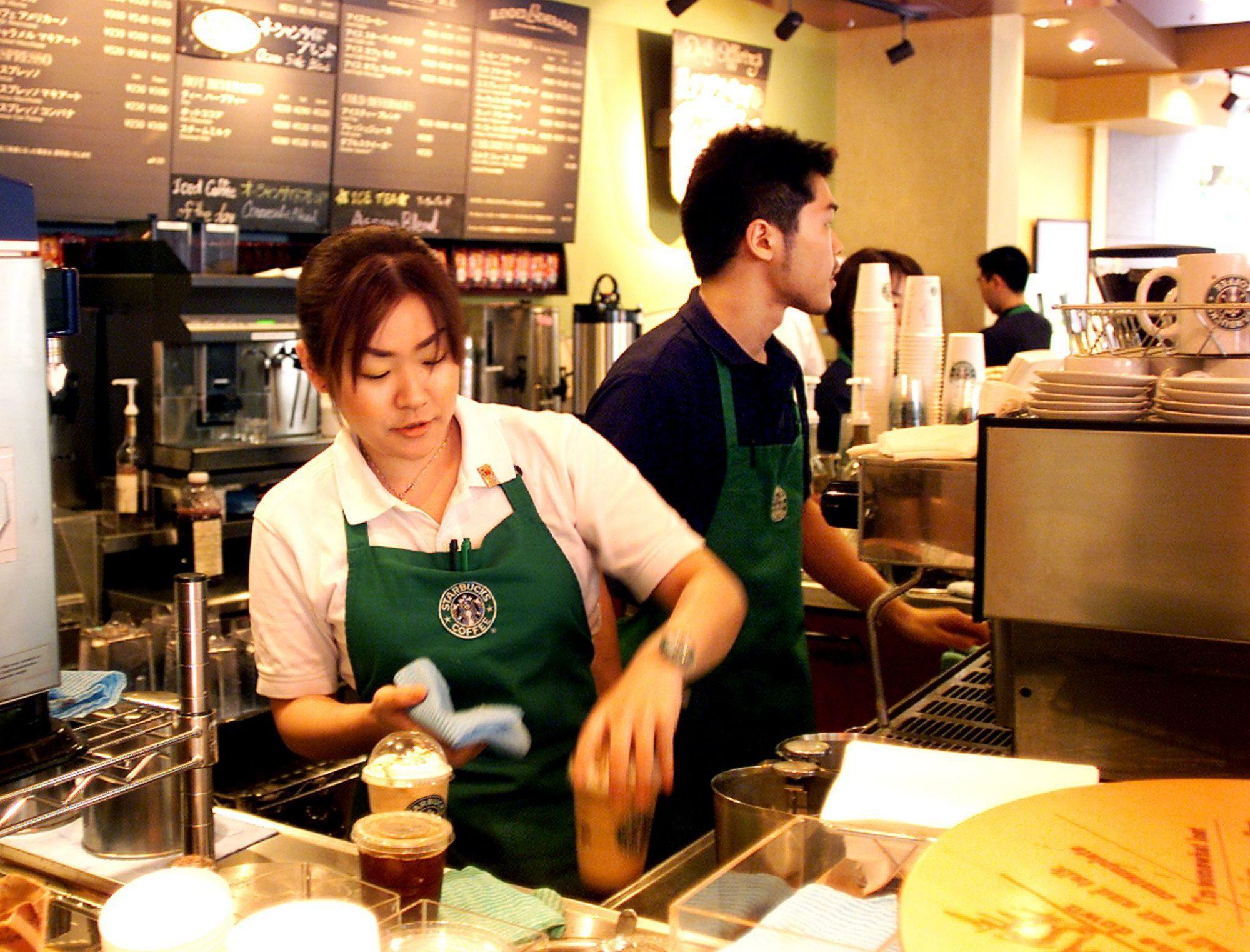 Clerks of a Starbucks Coffee store in Tokyo prepar