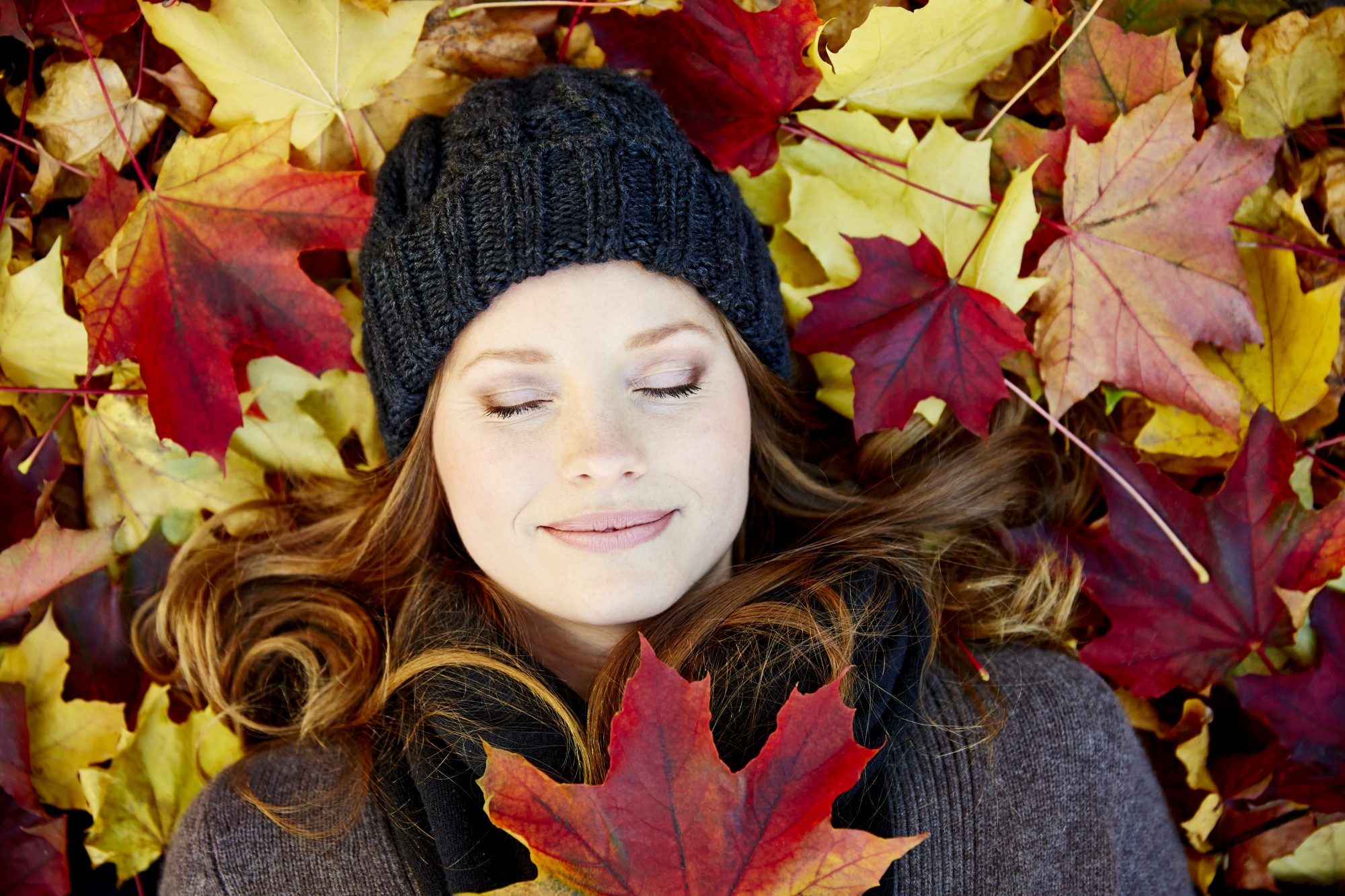 Germany, Hamburg, Woman lying with eyes closed on maple leaves in autumn, close-up