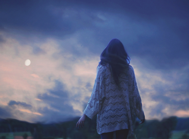 Woman wearing sweater walking outdoors at dusk under visible moon
