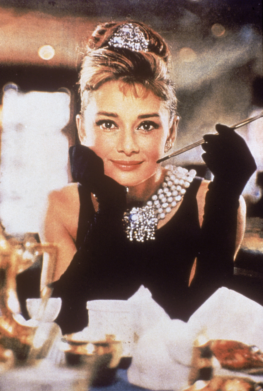 Belgian-born actress Audrey Hepburn (1929 - 1993), in a black, shoulderless dress, matching gloves, and a tiara, smiles with a cigarette holder in her hand, in her role as Holly Golightly the film, 'Breakfast at Tiffany's,' directed by Blake Edwards, New York, New York, 1961. (Photo by Paramount Pictures/Courtesy of Getty Images)