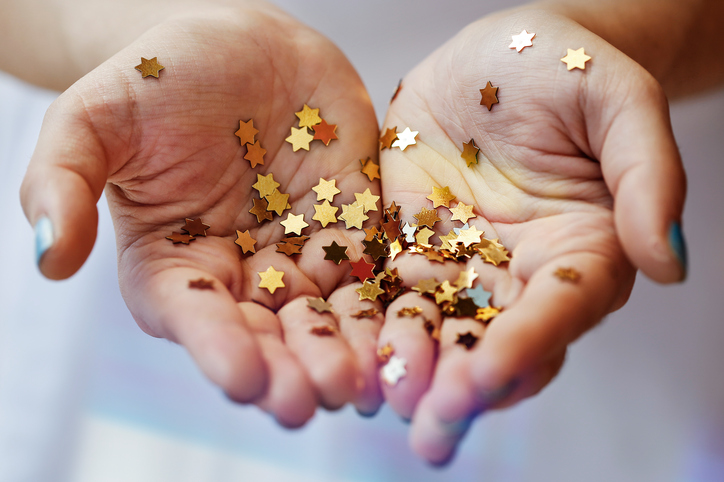 Girl holding gold star confetti