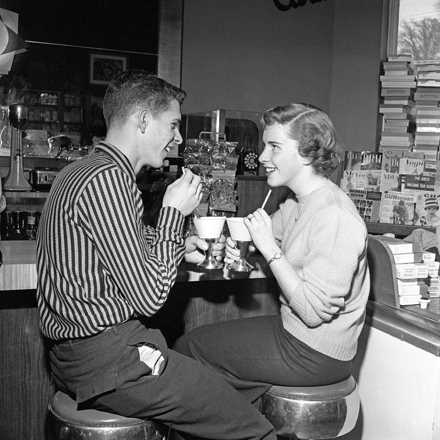 Teen Couple On Stools At Soda Fountain Drinking Sh