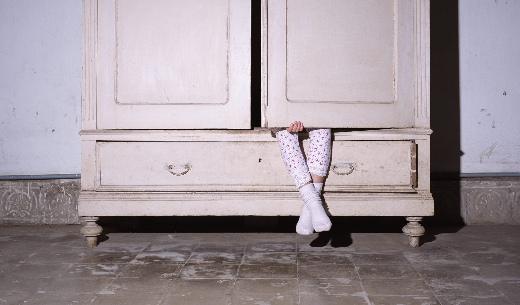 Girl (8-9) sitting inside wardrobe with door closed, low section