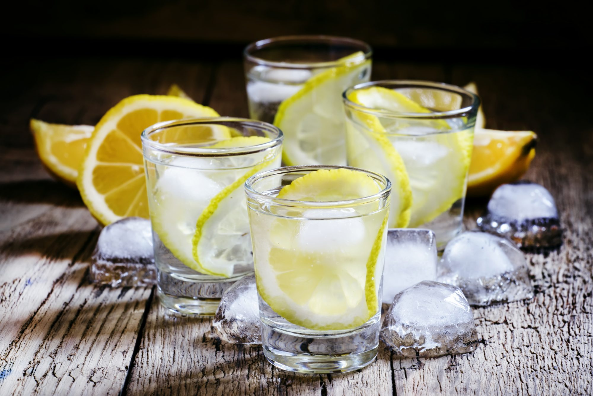 Cold Russian vodka with lemon and ice in shot glass