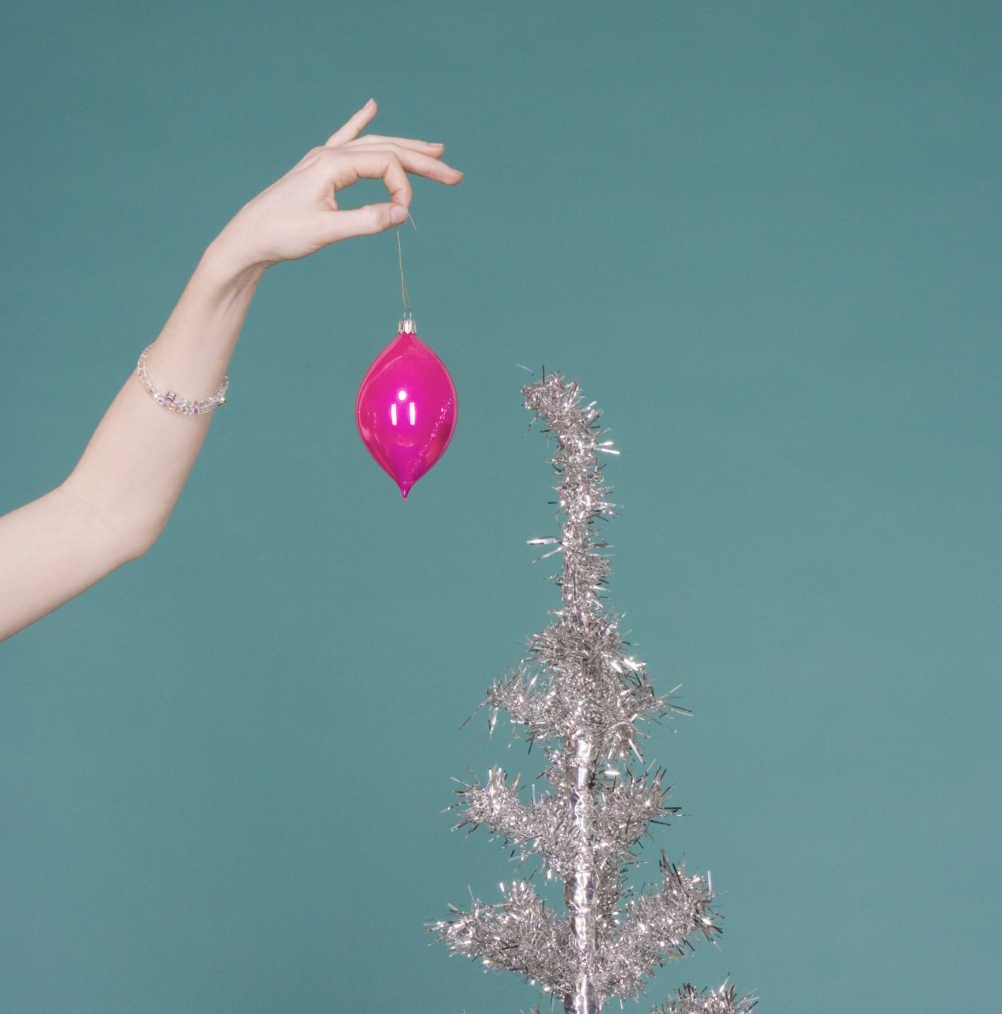 Woman putting Christmas decoration on artificial tree, close-up