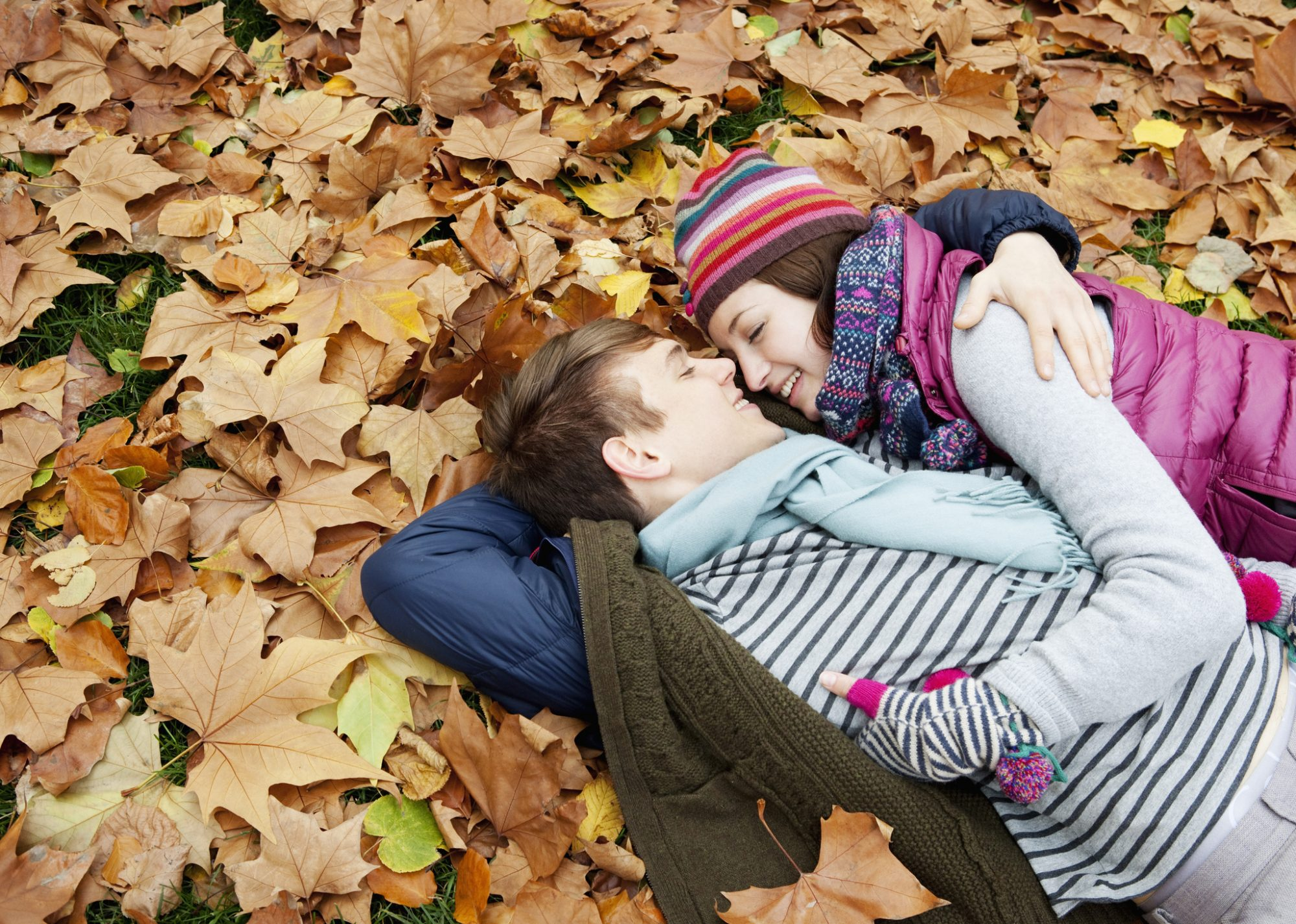 couple hugging,laying in autumnleaves in park.