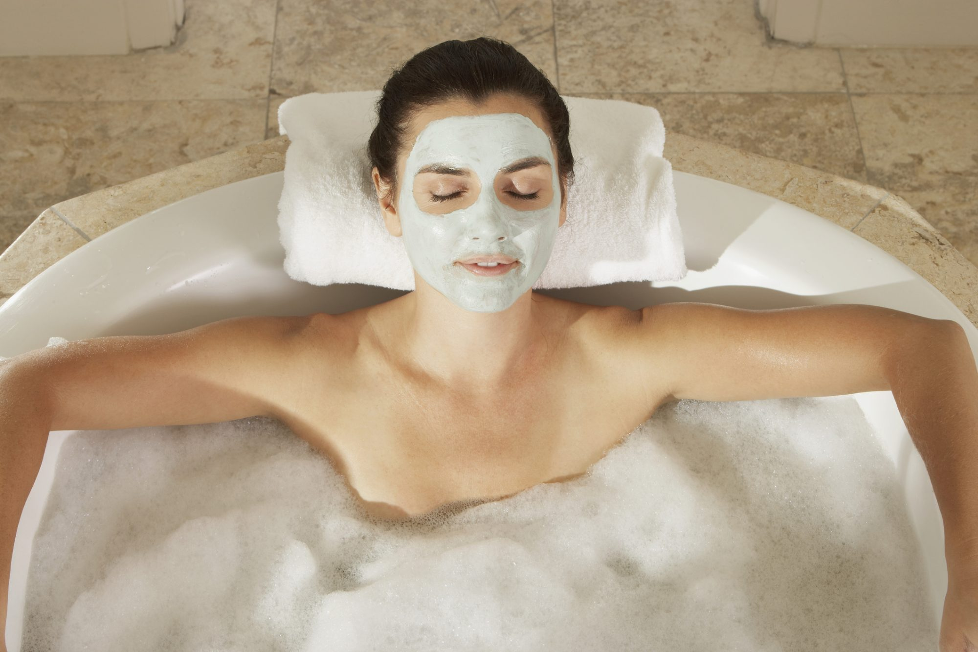 High angle view of a young woman in a bubble bath with her eyes closed