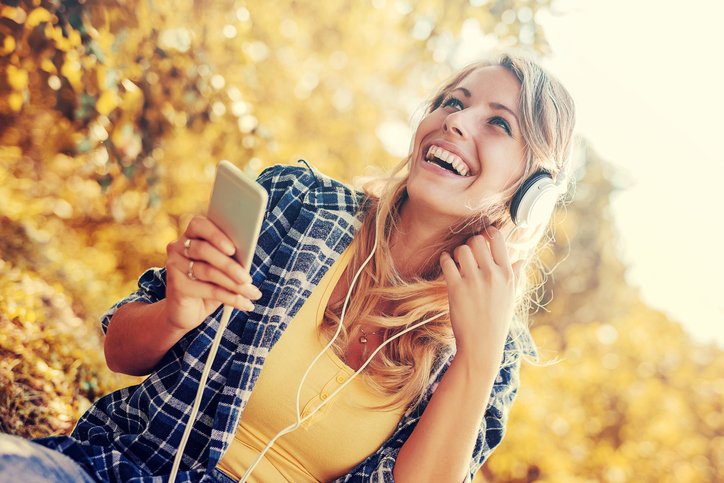 Young woman listening to music on smart phone