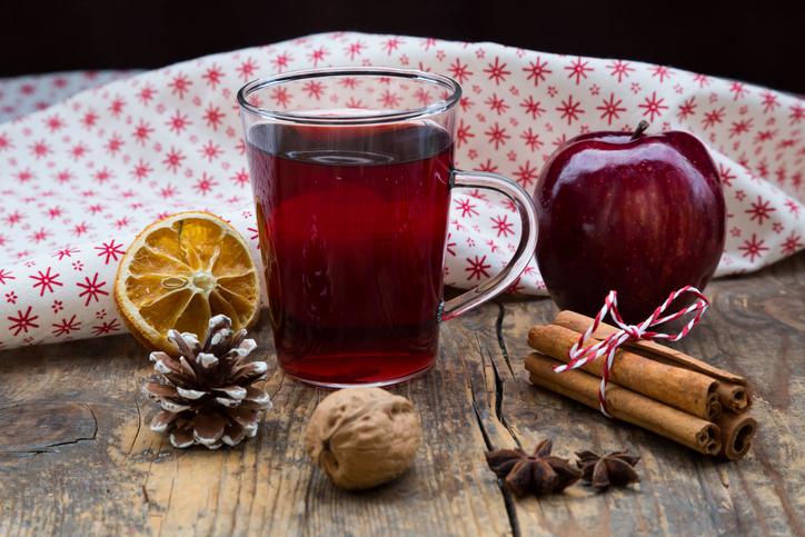 Glass of mulled wine, apple, cloth, walnut, cinnamon sticks and cinnamon stars