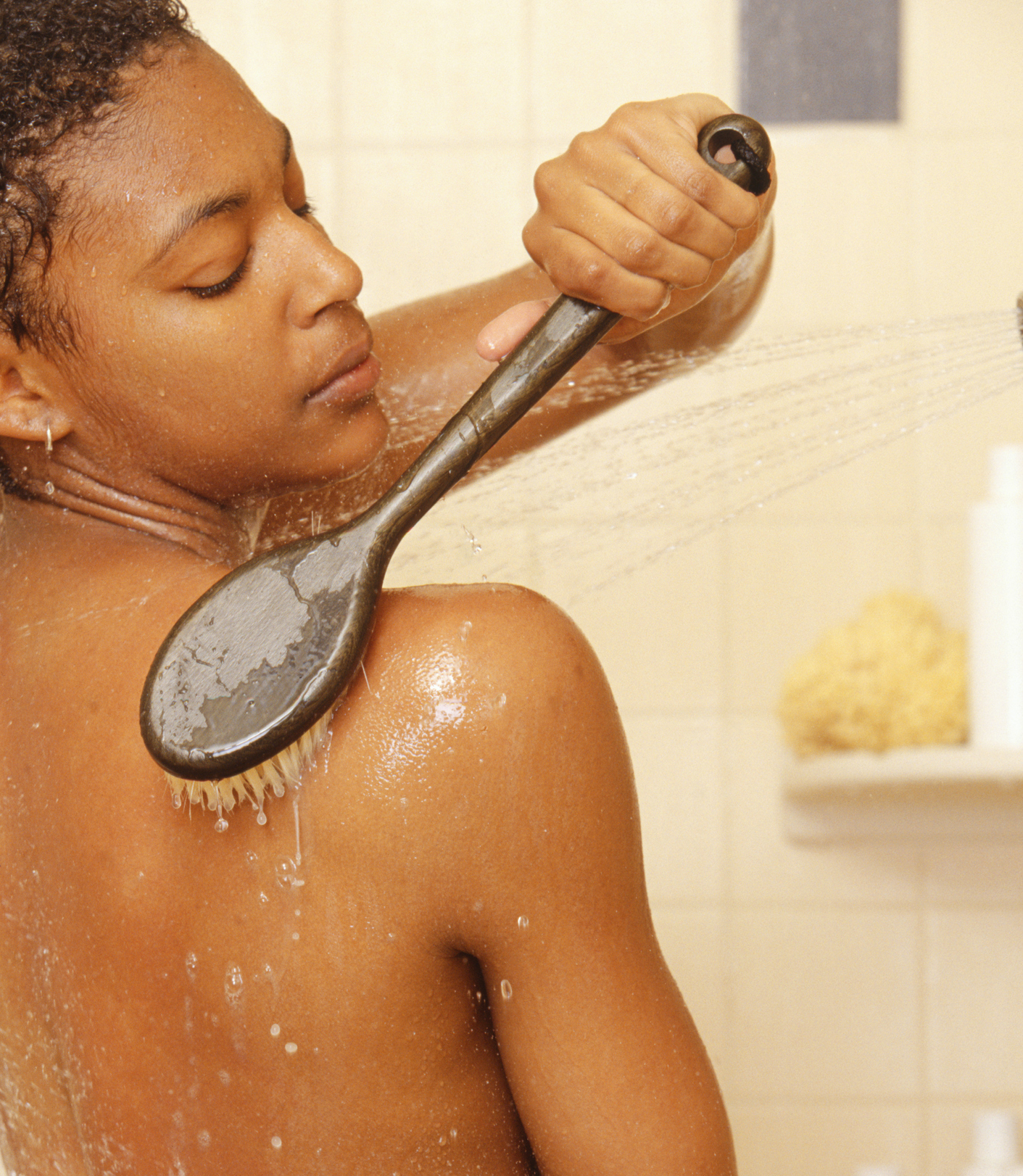 Woman brushing back in shower