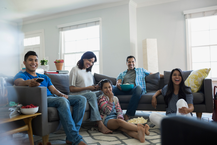 Family watching TV with popcorn in living room