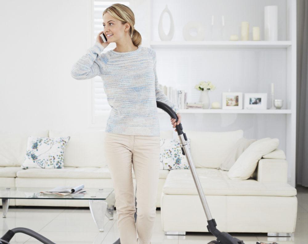 Distracted woman vacuuming dog