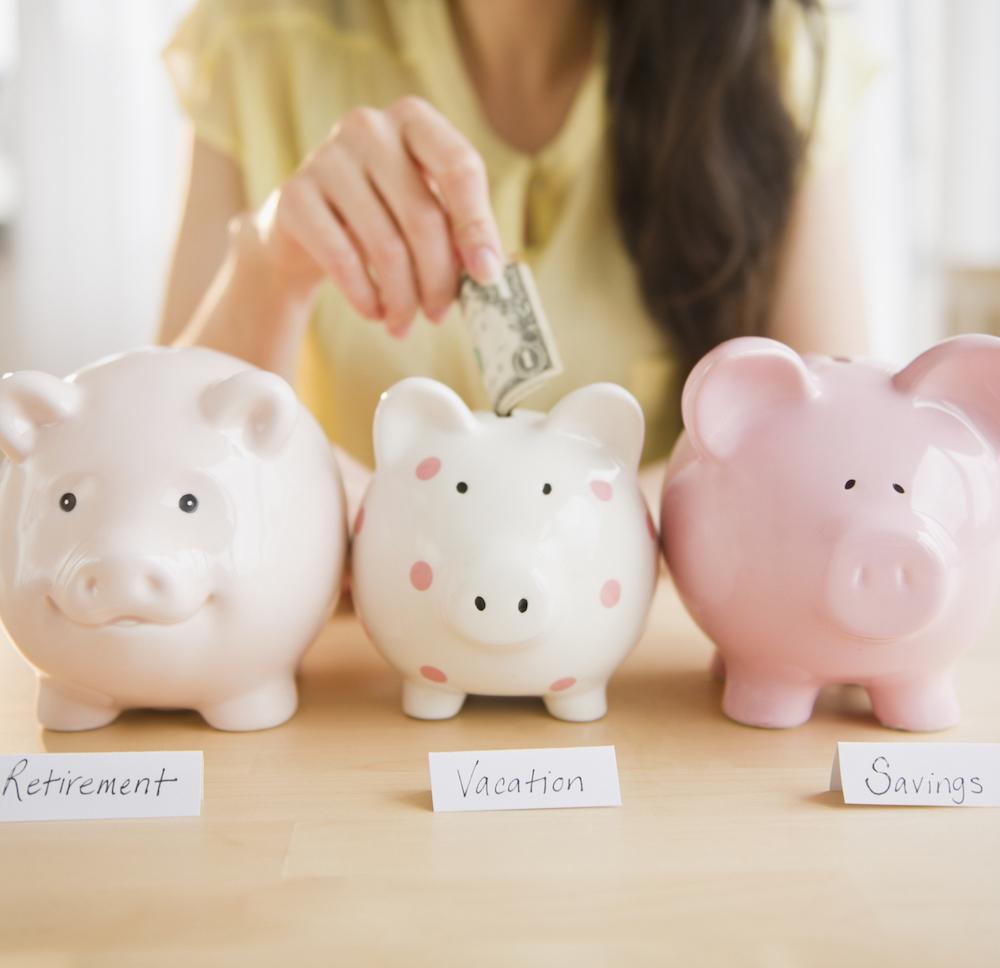 Mixed race woman putting money into piggy bank