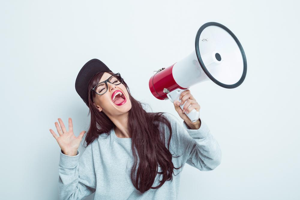 Young woman shouting into megaphone