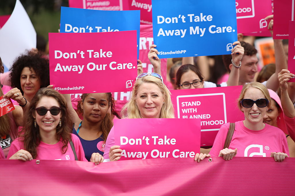 Participants hold pink Planned Parenthood banner and signs.