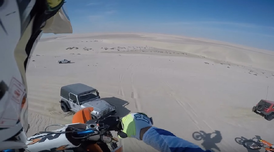 dirt biker jumps off sand dune into jeep