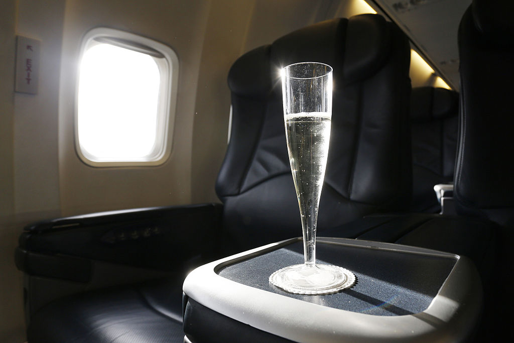glass of champagne on tray table in plane cabin