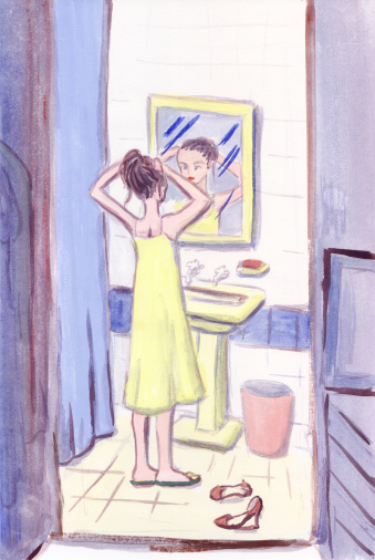A woman fixing her hair in a bathroom mirror