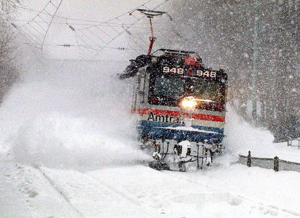 An Amtrak train blasts through a snow drift