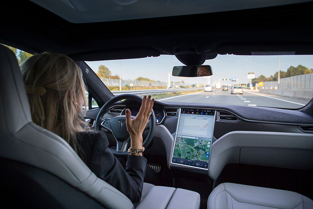woman driving tesla electric car