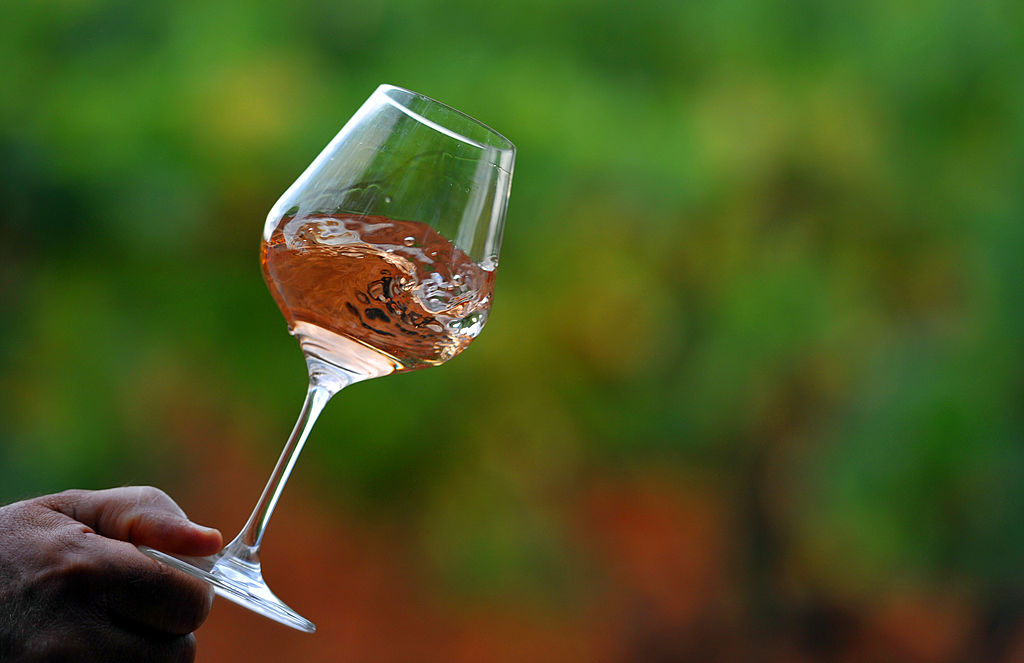 man holds glass of rose wine