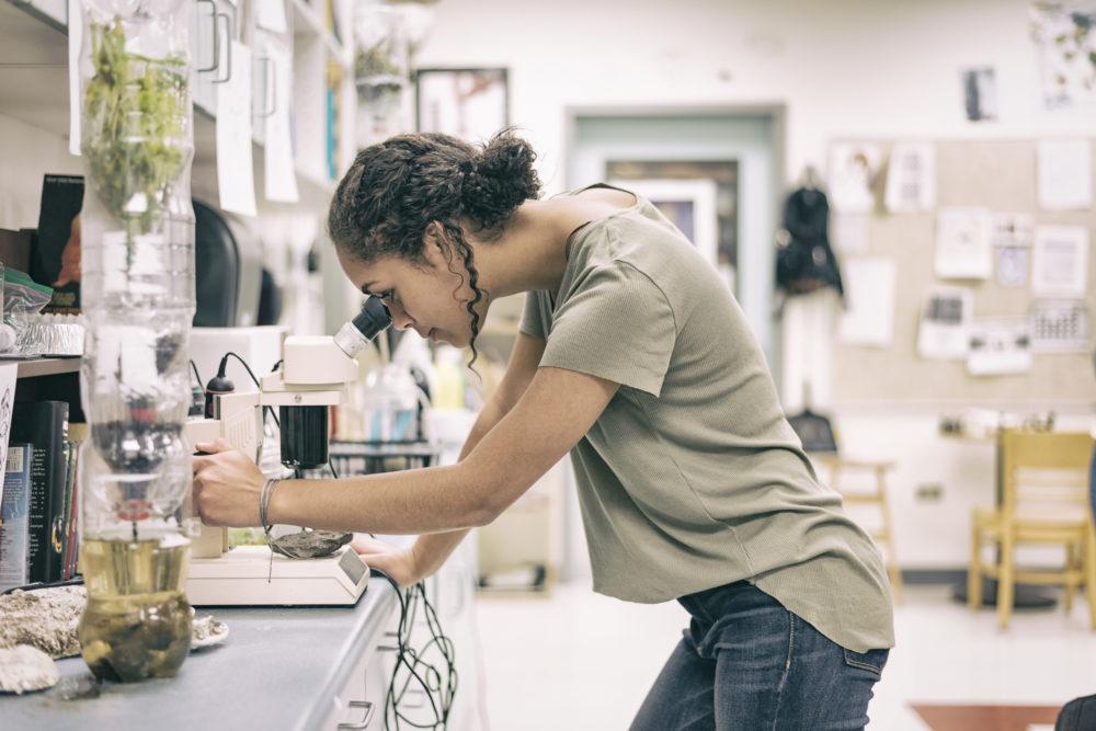 Teenage girl looking through microscope in science classroom