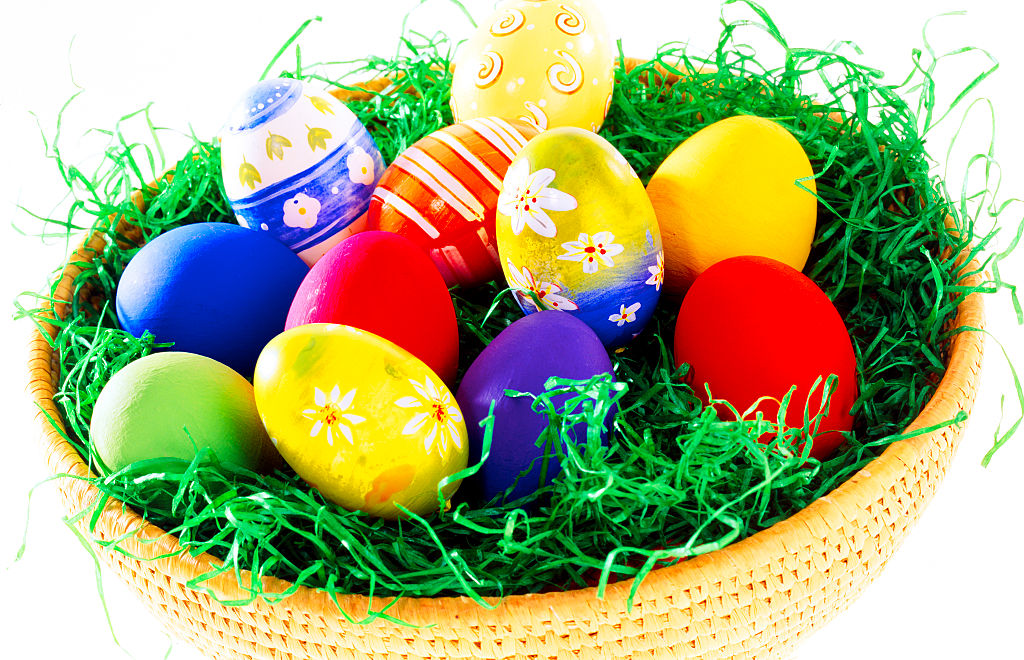 colored easter eggs in basket artificial grass