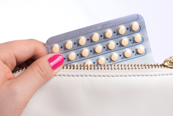 Woman hand pulling a contraceptive pills blister from a bag