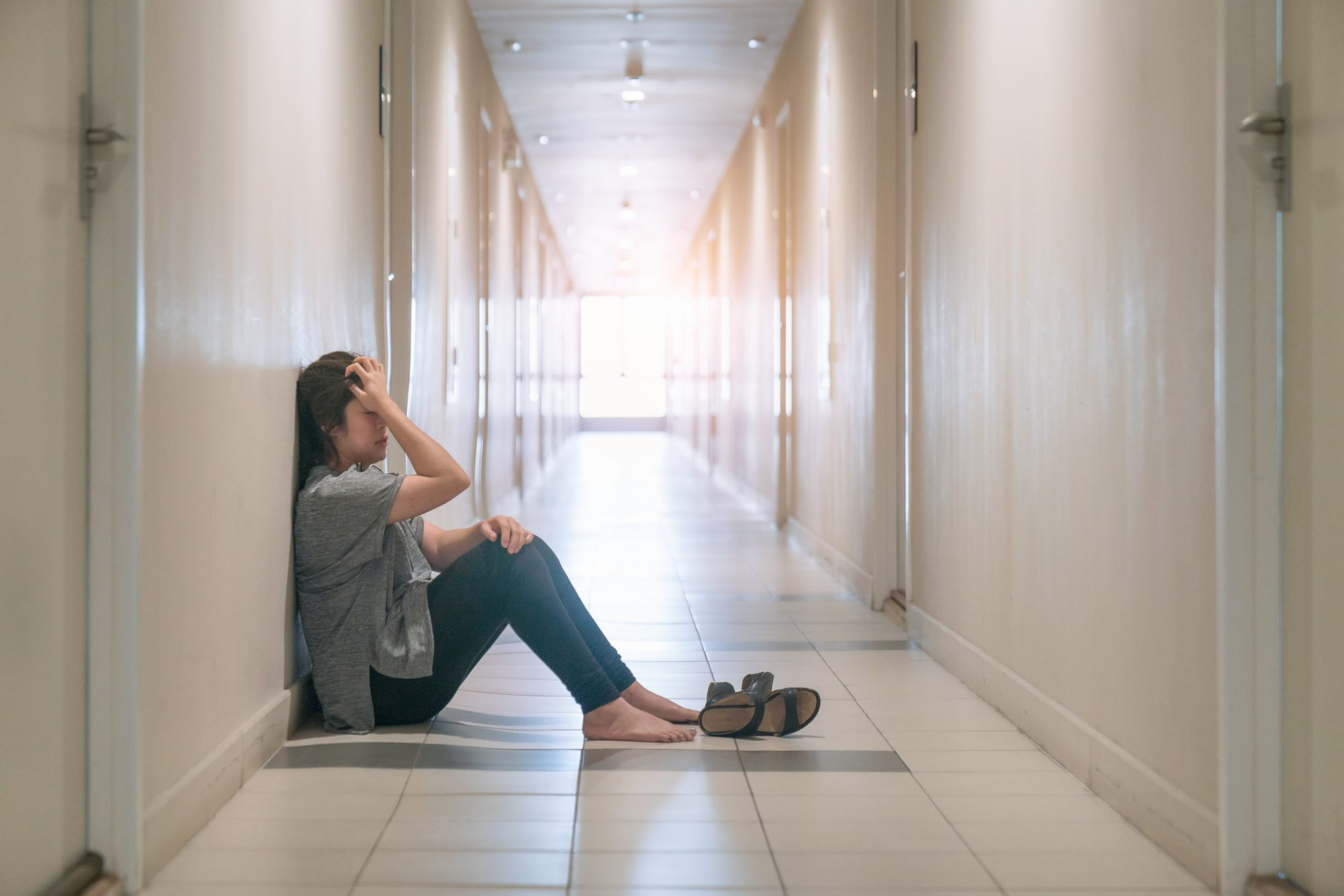 sad woman sitting in hallway
