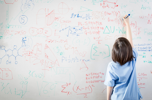 kid writing math equations on a white board
