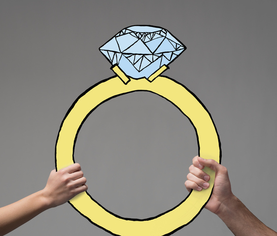 Two hands holding up a large illustrated engagement ring