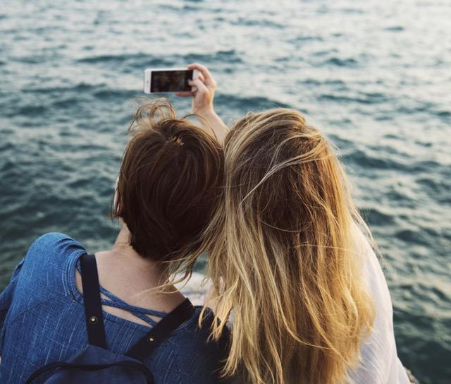 Two friends taking a selfie near the ocean