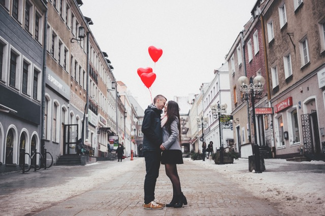 A couple kissing while holding heart balloons