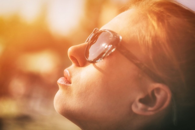 Woman looking into the sun with sunglasses