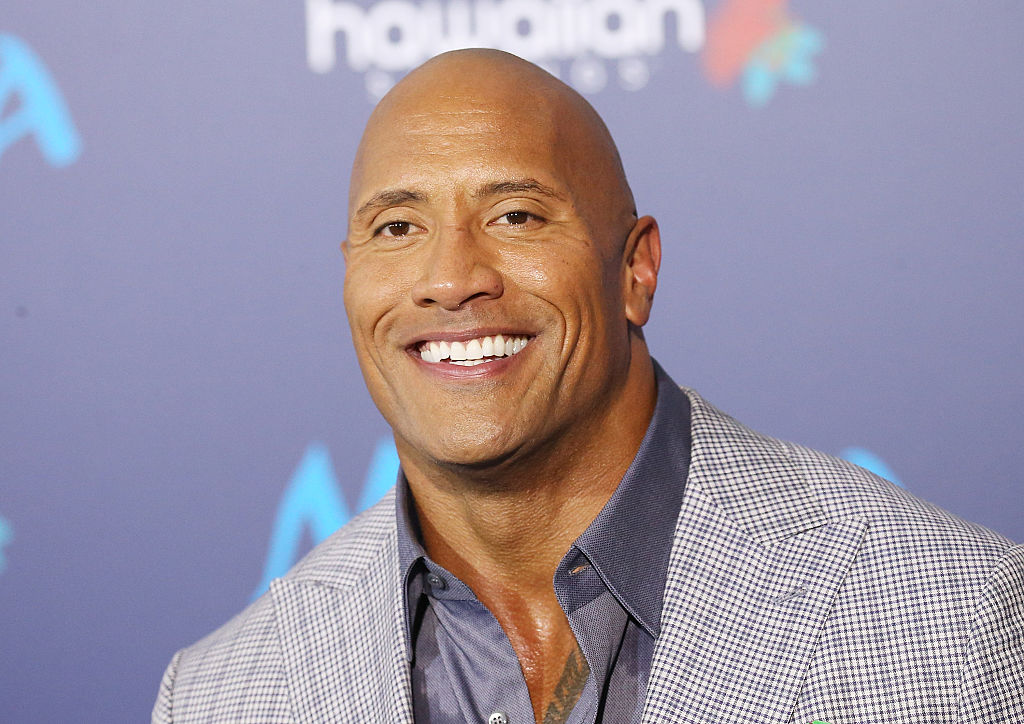 the rock smiling gray suit