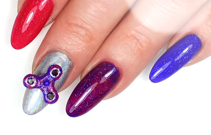 Hand with painted acrylic nails with a nail-sized fidget spinner