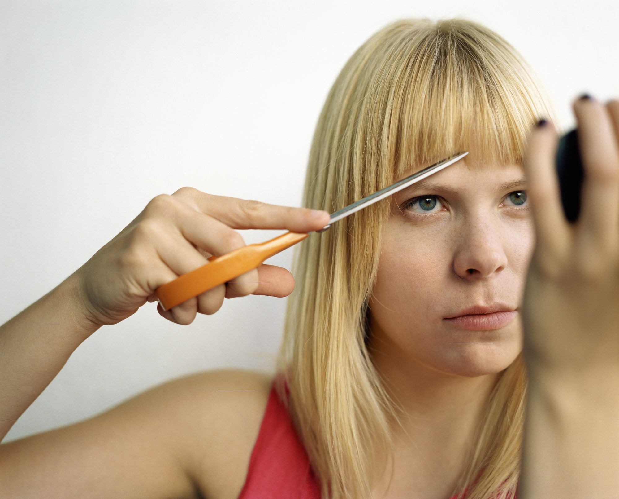 Image of a woman cutting her own bangs