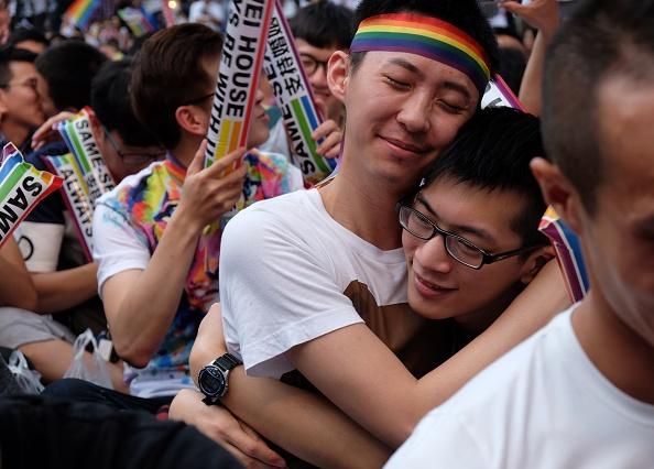 Two gay men hug at an LGBT gathering