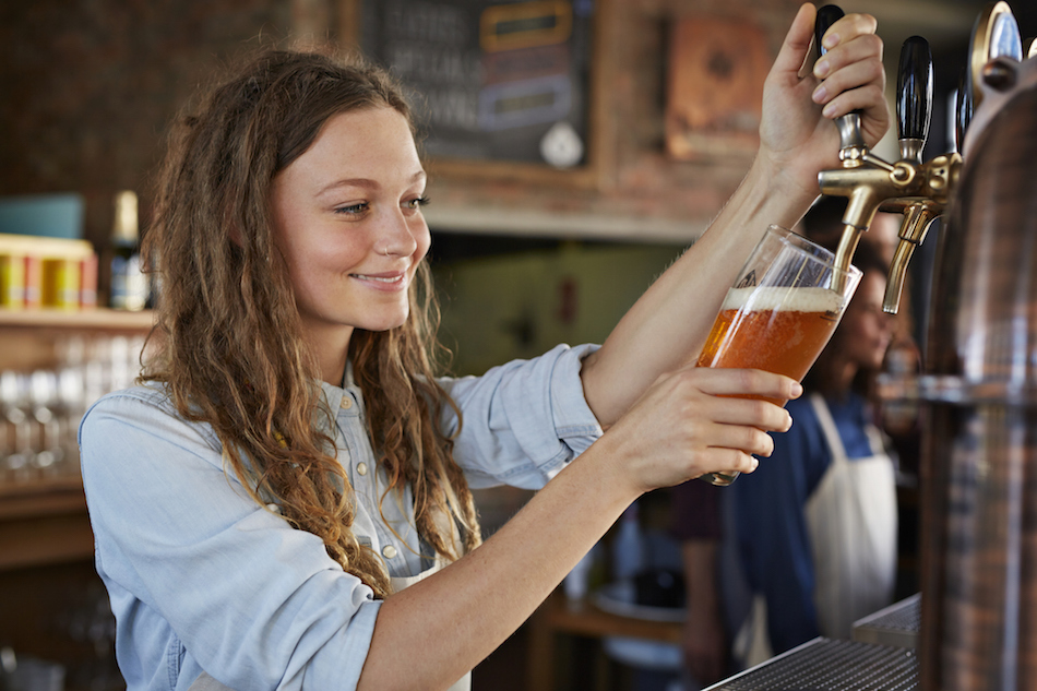 Portrait of smiling female bartender at microbrewery pouring beer