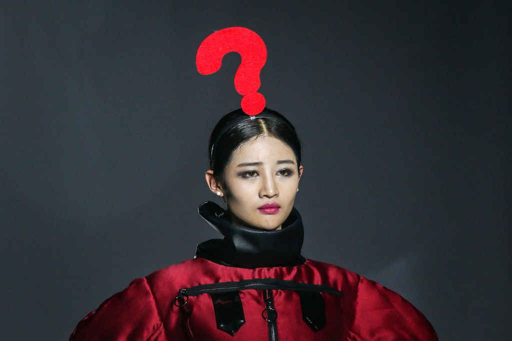 A model wears a giant question mark on her head on the runway during Wuhan Fashion Art Festival in China.
